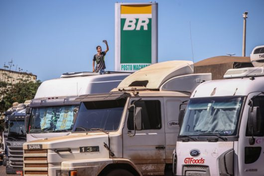 A driver takes a photograph of trucks parked at a Petroleo Brasileiro SA (PetroBras) gas station near on BR 040 highway during a protest against rising fuel prices in Luziania, Brazil, on Wednesday, May 23, 2018. Brazilian politicians, businesses and consumers are feeling the pinch on day three of a nationwide truckers'strikethat has prompted fuel shortages and bottlenecks at ports in one of the world's biggest commodity exporters. Photographer: Andre Coelho/Bloomberg via Getty Images