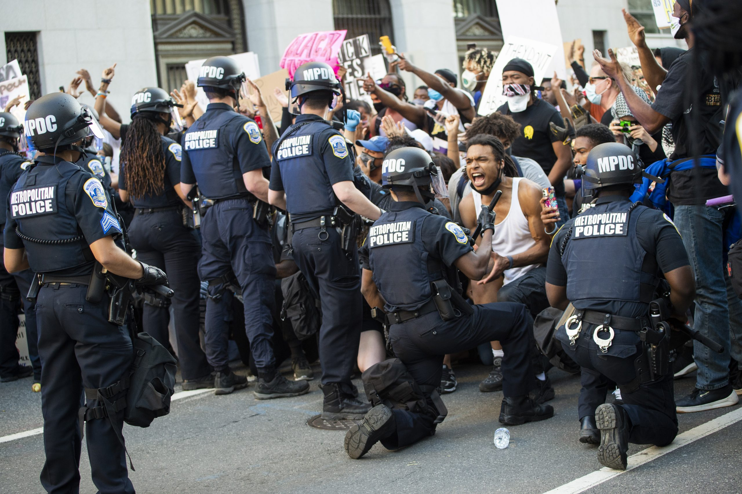 Em Nova Iorque, em Miami, em Portland (Oregon), em Lexington (Kentucky), e mesmo em Washington, policiais com equipamento de choque e guardas nacionais se ajoelham no chão entre os manifestantes. Ajoelhar-se é, desde 2016, um gesto adotado em protesto contra as mortes de negros pela polícia. Em outras cidades, em Flint (Michigan), em Nova Jersey, a polícia uniformizada se junta às manifestações e até levam os cartazes. Acima, policiais se ajoelham no chão perto da Casa Branca